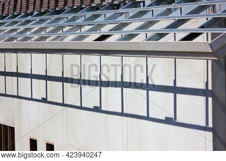 Light And Shadow Of Roof Truss Steel Structure On Cement Wall In Construction Site