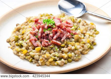 porridge of legumes with fried bacon and chive