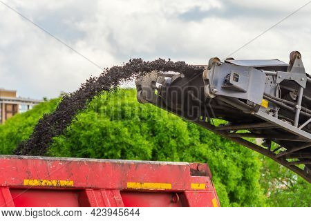 Road Cold Milling Machine Removes The Old Asphalt And Loading Into A Dump Truck. Repair Of Asphalt P