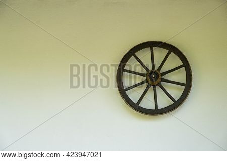 Old Wooden Wheel With A Metal Rim Hanging On The Wall Of An Old House