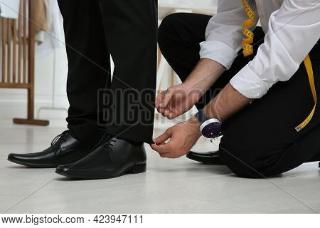 Professional Tailor Working With Client In Atelier, Closeup