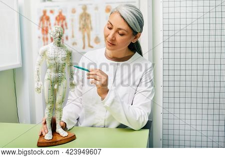 Mature Woman Acupuncturist, Doctor Of Traditional Chinese Medicine Showing Points On Acupuncture Mod