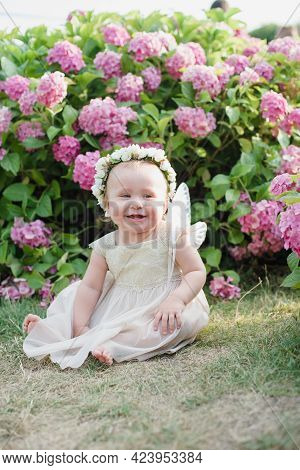 Girl With Butterfly Wings In Hydrangea Park. Beauty Imagination Fairy Tale Concept. Little Toddler G