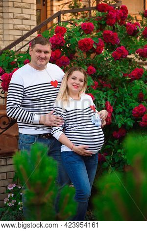 Young Pregnant Woman With Her Husband Outdoors.