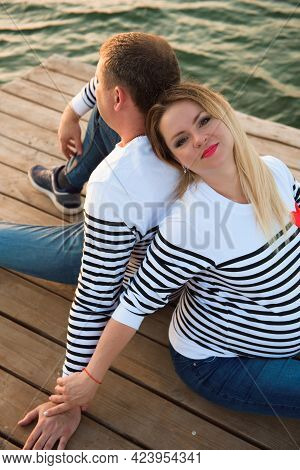 A Pregnant Mother And Her Husbant Relaxing On The Bridge By The River