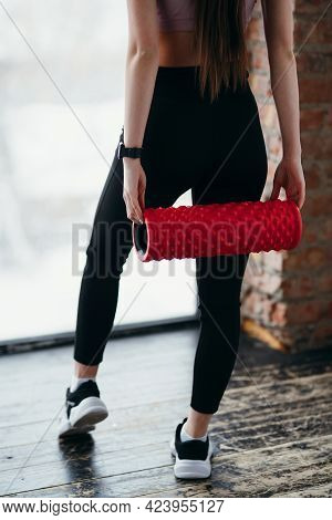 Photo From Behind. A Girl Standing In A Gym In Black Leggings Holds A Fascia In Her Hand For Trainin