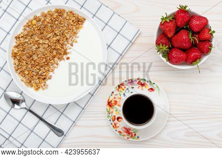 Muesli, A Cup Of Black Coffee And Strawberry On A Wooden Table. Hot Morning Drink. Dry Granola With