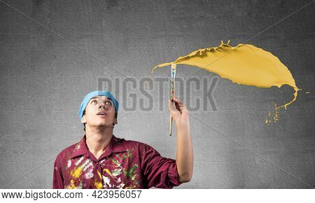 Young Artist Painting Yellow Brush Stroke. Male Painter In Dirty Shirt And Bandana With Paintbrush O