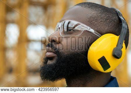 Profile of African builder in protective eyewear and earphones