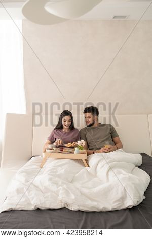 Young couple having breakfast in bed after sleep
