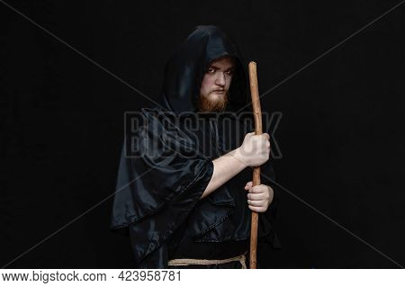A Monk In A Black Hood With A Staff On A Dark Background, A Gloomy Expression, A Medium Plan, Witchc