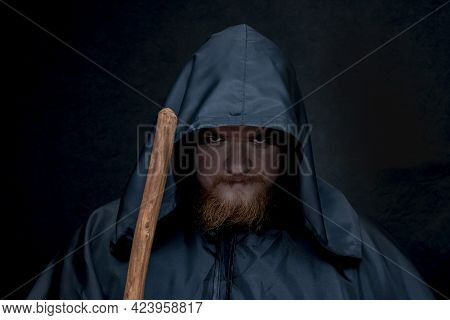 A Monk In A Black Hood With A Staff On A Dark Background, A Gloomy Expression On His Face, Witchcraf