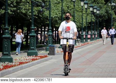 Moscow, Russia - June 2021: Guy In Protective Face Mask Rides An Electric Scooter In Alexander Garde