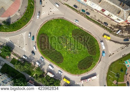 Top Down Aerial View Of Busy Street Roundabout Intersection With Moving Cars Traffic.
