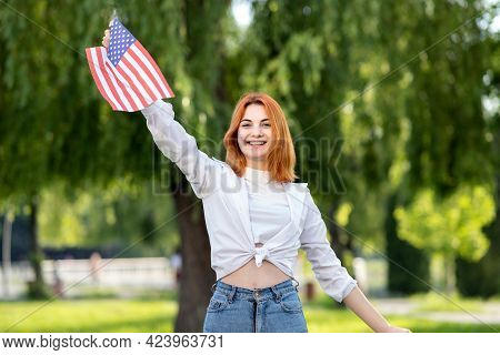 Angry Young Red Haired Woman Protester Posing With Usa National Flag In Her Hand Standing Outdoors I