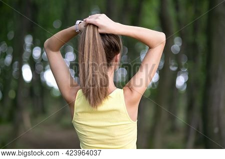 Young Woman Tying Her Long Hair Standing Outdoors.