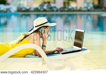 Young Woman On Beach Chair At Swimming Pool Working On Computer Laptop And Talking On Sell Phone In