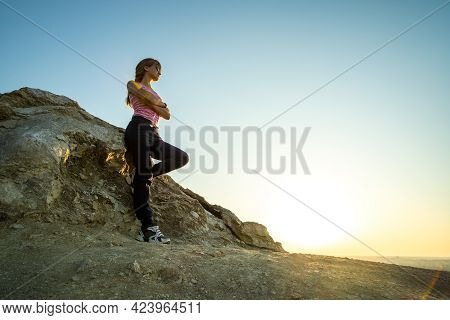 Woman Hiker Leaning On A Big Rock Enjoying Warm Summer Day. Young Female Climber Resting During Spor