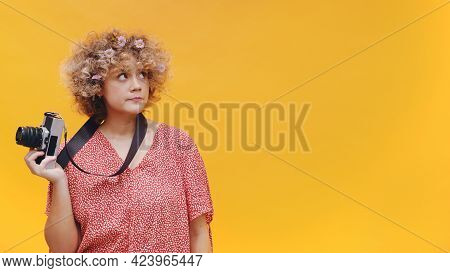 Attractive Young Photographer Isolated On Bright Yellow Background Studio. Camera Hanging From Her N