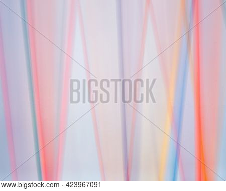 Colored Dowels Blurred Against A White Background In A Time Lapse Photo.