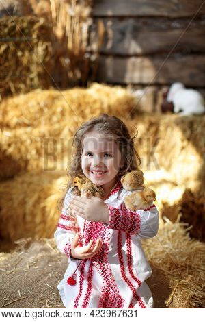 Cute Beautiful Girl Child In Ukrainian Embroidered Shirt In Bales Of Straw With Chickens And A White