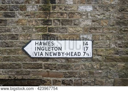 Directional Sign On A Stone Wall In The Village Of Dent, Cumbria, Uk