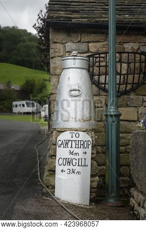 Dent, Cumbria, Uk, August 2020 - Directional Sign And Ancient Milk Churn In The Village Of Dent, Cum