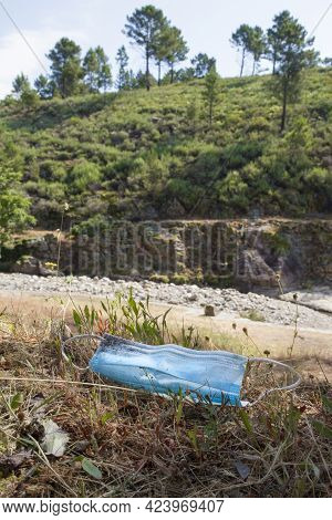 Surgical Face Mask Threw Out Close To Mountain River. Environmental Pollution In Nature Concept