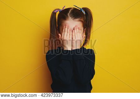 Embarrassed Shy Cute Girl With Ponytails Covering Her Face With Both Hands