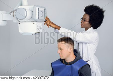 Young Afro American Female Radiologist Technician, Setting Up The Modern Machine To Take X-ray Scan,