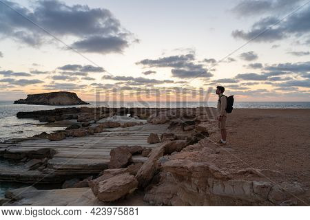 Sea Sunset View. Man With Backpack On Rocks With Beautiful View Of Yeronisos Island Near Coast Of Ag