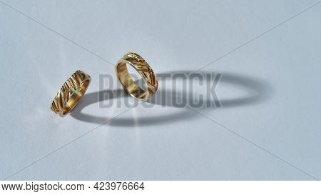 Pair Of Elegant Shiny Golden Rings With Carvings Standing On Light Background With Shadows, Widescre