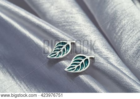 Stylish Sterling Silver Stud Earrings In Form Of Leaves Lying On Gray Silk Background. Jewelry Fashi