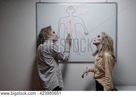 Two zombies discussing drwing of human body parts by white wall