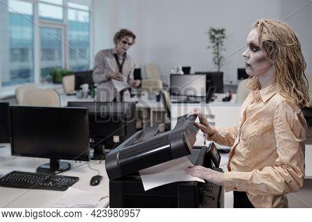 Zombie businesswoman using xerox machine in office