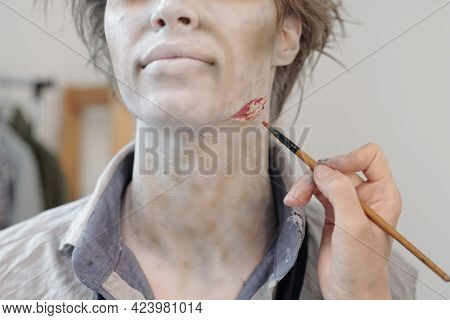 Hand of makeup artist with paintbrush making zombie visage on face of young man