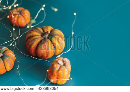 Handmade Four Pumpkins Of Different Shapes With Garland On Blue Background