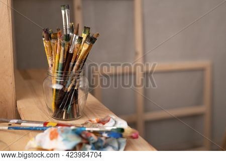 Painting palette and paint brush in glass jar on wooden table or windowsill. Paintbrush as art still life