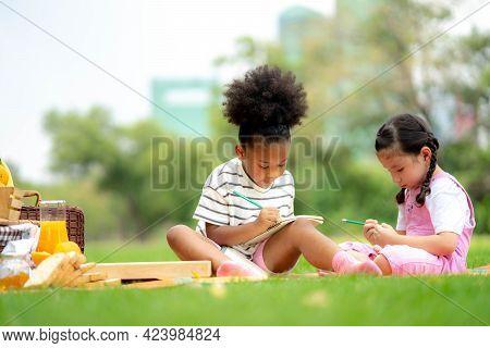 Kids Reading A Book In Summer Garden. Children Study. Boy And Girl Play In School Yard. Preschool Fr
