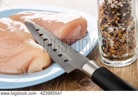 Kitchen Knife On Light-blue Plate With Pieces Of Raw Chicken Fillet, Transparent Jar With Condiment