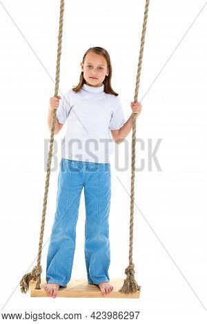 Preteen Girl Having Fun On Rope Swing. Happy Pretty Barefoot Girl Dressed Casual Clothes Standing On