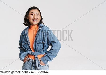 Happy smiling young asian brunette woman in denim jacket posing standing over gray background