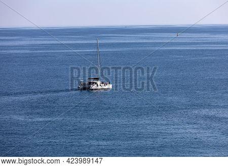 Polignano A Mare, Italy - September 17, 2019: White Catamaran Against The Blue Adriatic Sea In Polig