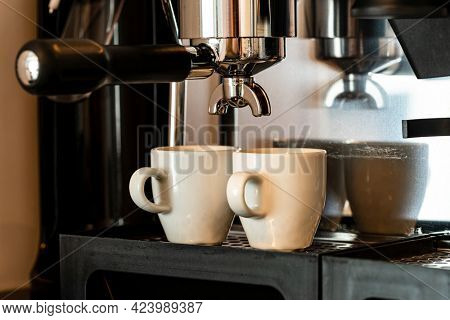 Close up image of professional espresso machine pouring in two cups