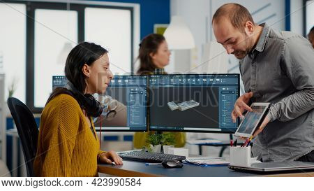Industrial Designer Holding Tablet Discussing With Woman Engineer While Working In Cad Program, Desi