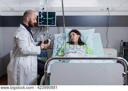 Physician Medic Monitoring Sick Patient During Medical Appointment In Hospital Ward. Doctor Discussi