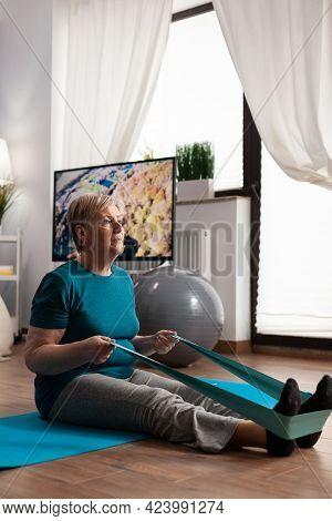 Focused Pensioner Wearing Sportswear Sitting On Yoga Mat Stretching Legs Muscle Using Fitness Elasti