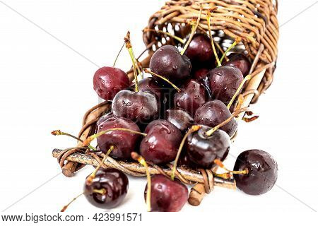 Overturned Wicker Basket With Ripe Sweet Cherries Spilling Out Of It On White Background, Close Up