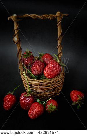 Wicker Basket Full Of Red Ripe Srtawberries On Dark Surface, Summer Food