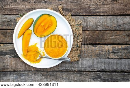 Top View Of Ripe Mango Pulp Or Aam Ras And Cuts In A Plate On Burlap Fabric Isolated On Wooden Backg